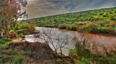golan : The River Jordan north of the Sea of GalileeLake Tiberius in Israel. The water is flowing away from the camera. The hillside in the background is covered with yellow, green and orange foliage, and the sky is just beginning to hint of a sun entering the we