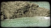 сбор винограда : Pan left of a rock that sticks up out of the water on an Italian beach. Vintage stylized video clip.