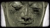 buddhismus : Zooming out shot of a Buddhas face. Vintage stylized video clip.
