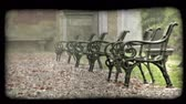 вещь : Shot of several park benches in a rain storm in Italy. Vintage stylized video clip.