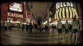 pecado : Many people walk across Vegas crosswalk with flashy casino lights in background at night in old downtown Las Vegas. Vintage stylized video clip.