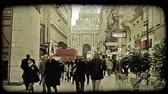 viyana : A crowd of Austrian townspeople walking on a sidewalk in between two buildings in Vienna. Vintage stylized video clip.