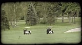 kordé : Two golf carts, one with two people and one with one person, follow each other along cart trail in  green golf course lined with various types of trees and containing sand pit to the right. Vintage stylized video clip.