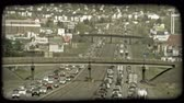 congestionamento : Time lapse far shot of congested traffic along city highways, opposite directions running parallel to each other with highway overpasses above both highways and suburban neighborhoods and businesses in background. Vintage stylized video clip.