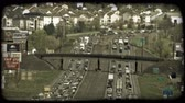 passagem elevada : Time lapse medium shot of congested traffic along city highways, opposite directions running parallel to each other with highway overpasses above both highways and suburban neighborhoods and businesses in background. Vintage stylized video clip.