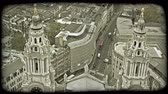 Лондон : Overlook from high viewpoint down to two spires of a church or municipal building with ornately designed architecture and streets below tall building-lined passages and intersections. Vintage stylized video clip. Стоковые видеозаписи