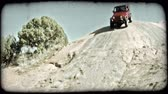 duro : Red jeep descends carefully down a slickrock hill nearby red dirt and sand and sparse trees in Moab, Utah on a sunny day. Vintage stylized video clip.