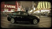 hybridní : Pan of black shiny hybrid car as it drives over crosswalk along las vegas boulevard with flashy casinos and lights in background in old town Las Vegas at night. Vintage stylized video clip.