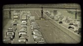 passagem elevada : Time lapse of congested traffic along city highways, opposite directions running parallel to each other with highway overpass above both highways. Vintage stylized video clip.