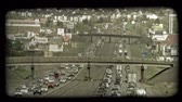 hádka : Time lapse far shot of congested traffic along city highways, opposite directions running parallel to each other with highway overpasses above both highways and suburban neighborhoods and businesses in background. Vintage stylized video clip.
