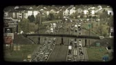 congestionamento : Time lapse medium shot of congested traffic along city highways, opposite directions running parallel to each other with highway overpasses above both highways and suburban neighborhoods and businesses in background. Vintage stylized video clip.