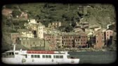 italiano : A ferry full of tourists travels down a rocky Italian coast line. Vintage stylized video clip.