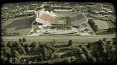 espaçoso : Aerial shot over University of Utah football stadium and outerlaying buildings and neighborhoods lined with trees. Vintage stylized video clip.