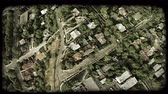 habitação : Wide-angle aerial shot directly over middle-income neighborhoods with streets lined with trees. Vintage stylized video clip.