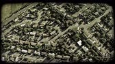 habitação : Wide-angle aerial shot of middle-income neighborhoods with streets lined with trees, including neighborhood park and school. Vintage stylized video clip. Stock Footage