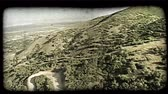 ассортимент : Aerial shot over Wasatch Mountain range hills and unpaved, winding dirt mountain road near Salt Lake City, Utah. Vintage stylized video clip.