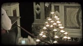 santuário : People take pictures and worship at a candle holder inside a cathedral in Italy. Vintage stylized video clip.