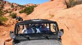 wydmy : Motion view of boys in a jeep driving over the big rocks in Moab Utah on a beautiful sunny day. Wideo
