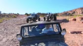 экспедиция : Motion view of boys in a jeep driving over the big rocks in Moab Utah on a beautiful sunny day. Стоковые видеозаписи