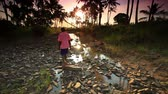акация : Boy walks along rocky stream with background of trees under African sunset