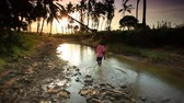 акация : Kid washes clothes in rocky stream with background of trees under african sunset