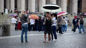 база : Some women at St. Peters Square holding umbrellas and taking pictures. Shot in the Vatican City.