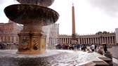 база : The middle of St Peters Square, including its obelisk, from the near one of the fountains of the piazza. Tourists with umbrellas walk around the obelisk, and the columns are visible in the background. Стоковые видеозаписи