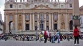 база : Tourists walking around and taking pictures of the Piazza San Pietro. Behind them is the facade of the Basilica of St Peter, though the dome is not visible. Стоковые видеозаписи
