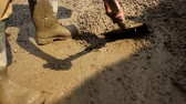 concentrando : Close up of someone in boots using a shovel to stir and move muddy gravel. Stock Footage
