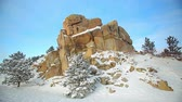 harikalar diyarı : Stationary view of a beautiful rock formation with a few pine trees along the sides covered in snow, located in Wyoming.