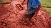 lamacento : Close up of mans feet stepping on red clay to mix it for brickmaking. Footage zooms out to show the man and his surroundings. Filme din Kenya, Africa.