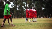 официальный : A team of African boys in red football uniforms gather in a huddle on a grass field. Other young men walk by. Filmed in Kenya, Africa.
