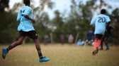 официальный : Footage following the action of a Kenyan footballsoccer game between two teams of young men, a light blue team and a blue team. Filmed in Kenya, Africa.