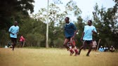 fitness : Footage following the action of a Kenyan footballsoccer game between two teams of young men, a light blue team and a blue team. Filmed in Kenya, Africa.