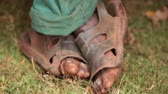 close ups : Close up of crossed, muddy feet wearing muddy sandals. Filmed in Kenya, Africa.