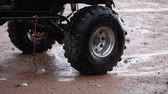 экспедиция : Stationary view of jeep tires up close with the under carriage dripping water and the surrounding sand wet and muddy, located in Moab Utah.
