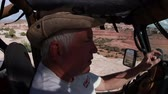 экспедиция : Passenger side view of an older man in the drivers seat of a jeep talking on walkie talkie while driving , shot on a beautiful sunny day in Moab Utah. Стоковые видеозаписи
