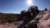 wydmy : Moving shot of a white Jeep slowly driving down off a large rock in Moab, Utah. Wideo