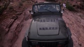 lamacento : View of the front of a Jeep as is climbs up rocks in Moab, Utah. Men stand beside it and another Jeep can be seen on a lower level of rock.