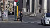 vista : Two women wait for the traffic signal as cars pass by and other pedestrians cross. Street view filmed in Rome, Italy.