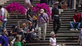база : Camera follows the descent of a uniformed man down the Spanish Steps. The Steps are covered with pink flowers and tourists. Rome, Italy, May, 2012.