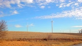 iowa : Stationary shot of windmills in an open field with a beautiful cloudy blue sky background, located in Iowa.