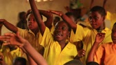 placa : Close up of boys raising his hand in a full classroom in Kenya, Africa. Front view.