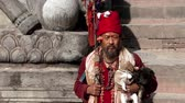 male animal : Old Nepali man holding puppies sits on stone steps in Nepal