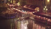 тент : Dock with stairs up to a seating area where many people are sitting. Lights adorn the awning and they glint off the water. The scene begin out of focus then racks into focus. Shot on May 2,2012 in Venice,Italy