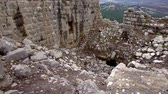 battlements : Dolly slider move right to left of the absolute ruin of part of Nimrod Fortress in the Golan Heights region of Israel. The wall on the left part of the donjon, or keep is still standing but the collapse of the structure in the right side of the frame  Stock Footage