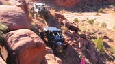 экспедиция : Motion high angle view of a jeep towing another jeep with passengers walking behind, located in Moab Utah.