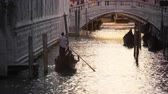 canal navegável : Gondolier navigating toward a busy canal bridge. Shot on May 3,2012 in Venice,Italy