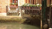 parecer : Flower boxes and wrought-iron fence along the waterside of a canal. Step come up from the water, but do not seem to lead anywhere. The sunlgiht dances on the greenish water. Shot on May 2, 2012 in Venice, Italy.