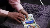 europe : Slow motion shot of the hands of a male tarot card reader shuffling and fanning the cards in the street of Rome. Shot with a high speed camera on May 5,2012